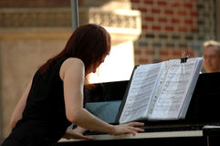 Playing piano. Young woman playing piano during live concert Stock Photography