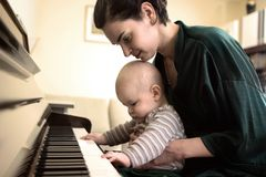 Playing the piano. It is a very intimate moment. A baby is enjoying the piano while his mother is seeing after him stock photography