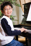 Playing piano. A shot of an asian boy playing piano Stock Images