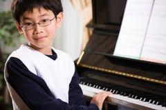 Playing piano. A shot of an asian boy playing piano Royalty Free Stock Photo