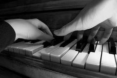 Playing the Piano, Black-and-white. A close take on two hands playing the piano with shallow focus Stock Photography