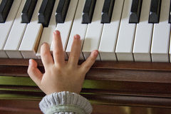 Playing The Piano. The child's hand are playing the piano stock photography