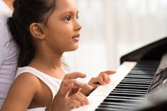 Playing the piano. Close-up of little Indian girl playing the piano Royalty Free Stock Photo