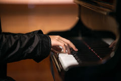 Playing Piano. Close up of a man's hands playing a piano in church Royalty Free Stock Photo