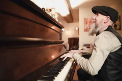 Playing A Piano For The Guests. Senior man is entertaining wedding guests by playing on piano Stock Photography