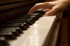 Playing the piano - hand on keys Stock Photo