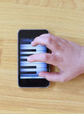 Playing piano on phone. Playing piano on modern touch screen phone stock image