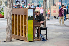 Playing piano in public. Upright wood pianos are placed throughout the 16th street mall in Denver, inviting people to entertain, relax, or just enjoy music in Stock Photography