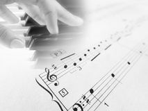 Playing piano sheet music notes. Faint image of a hand playing the piano and piano music script in the foreground with musical notes and symbols on white clean stock photography