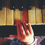 Playing the piano. Small baby hand playing the piano Stock Photography