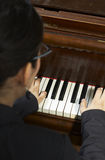 Playing Piano Teacher. Portrait of a female piano teacher as she plays piano.  Shot from back view, high viewpoint Stock Image
