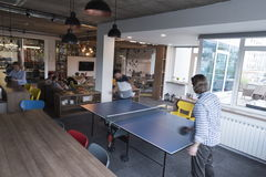 Playing ping pong tennis at creative office space Stock Image