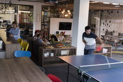 Playing ping pong tennis at creative office space. Two young start up business men playing ping pong tennis at modern creative office space  people group have Royalty Free Stock Images