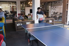 Playing ping pong tennis at creative office space. Two young start up business men playing ping pong tennis at modern creative office space  people group have Royalty Free Stock Image