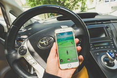 Playing Pokemon Go game. KAUNAS, LITHUANIA - JULY 18, 2016: Person holding mobile phone and playing Pokemon Go game in a car. Pokemon Go is a location-based Royalty Free Stock Photos