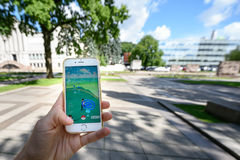 Playing Pokemon Go game. KAUNAS, LITHUANIA - JULY 18, 2016: Person holding mobile phone and playing Pokemon Go game. Pokemon Go is a location-based augmented Stock Photography