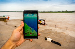 Playing pokemon go at riverbank in india Stock Photography