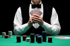 Playing poker. A man with bow tie playing poker Royalty Free Stock Images