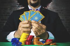 Playing poker and betting with chip. Businessman gambling with poker cards in the casino and betting with stack of chip on the table royalty free stock photography