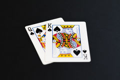 Playing poker cards queen king on black background Stock Images