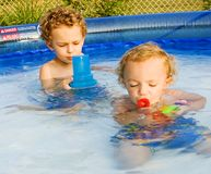 Playing in the Pool. Young boys playing in swimming pool in back yard Royalty Free Stock Photography