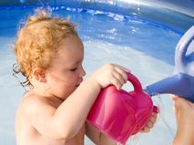 Playing in the Pool. Young boy playing in swimming pool with watering can Stock Photos