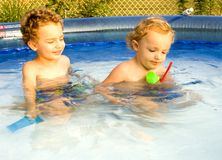 Playing in the Pool. Two young boys playing together in swimming pool Royalty Free Stock Image