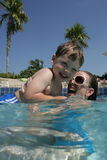 Playing in the pool. Young boy being held by a woman in a pool, both smiling, caucasian/white Royalty Free Stock Images