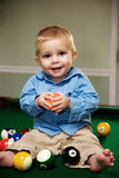 Playing with pool balls. A little boy playing on the pool table Royalty Free Stock Image