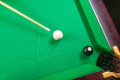 Playing pool. Close-up of someone aiming the billiard ball with cue Royalty Free Stock Photography