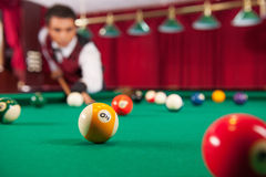Playing pool. Confident young man aiming the billiard ball with cue Royalty Free Stock Photos