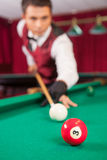 Playing pool. Confident young man aiming the billiard ball with cue Stock Images
