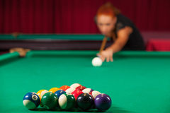 Playing pool. Confident young man aiming the billiard ball with cue Stock Photos