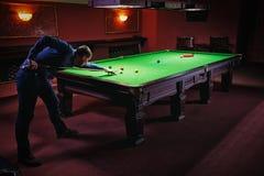 Playing pool, man aiming the billiard ball. Snooker Stock Photo