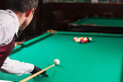 Playing pool. Rear view of man aiming the billiard ball with cue Royalty Free Stock Photography