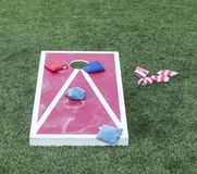 Red and white cornhole game. Playing the populare game corn hole on a red and white wood board with blue and red striped bean bags on turf stock photo