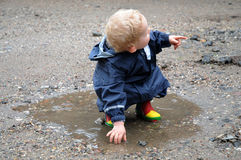 Playing in a puddle. Little boy with rain wear and rubber boots playing in a puddle royalty free stock photos