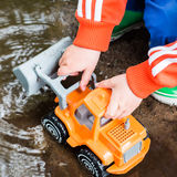 Playing in the puddle. Children playing with plastic toy in puddle stock image