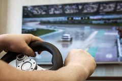 Playing in the race behind the wheel of a game console. In front of the big screen Royalty Free Stock Image