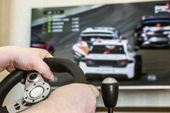 Playing in the race behind the wheel of a game console. In front of the big screen Stock Photos