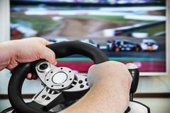 Playing in the race behind the wheel of a game console. In front of the big screen Royalty Free Stock Photos