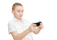 Playing racing game. Boy is playing racing game on touchscreen smartphone Stock Photo