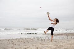 Playing racket ball. Young woman playing racket ball on the beach Royalty Free Stock Photos