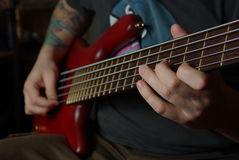 Playing an red bass guitar Royalty Free Stock Photos
