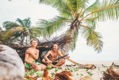 Playing in Robinzones: father and son built a hut from palm tree Royalty Free Stock Images