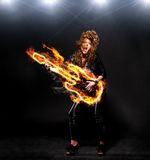 Playing rock music. Woman is playing rock music on fiery guitar Stock Image