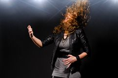 Playing rock music. Woman is playing rock music on air guitar Stock Photo