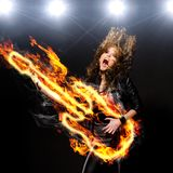 Playing rock music. Woman is playing rock music on fiery guitar and singing Stock Photo