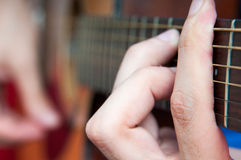 Playing rock music. Singer hands on the acoustics guitar playing a rock  song Royalty Free Stock Image
