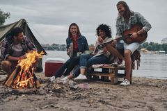Playing romantic song. Group of young people in casual wear smiling while enjoying beach party near the campfire royalty free stock photography
